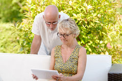 Middle age couple, smiling, using a tablet. In their garden stock photo