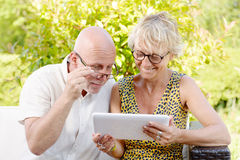 Middle age couple, smiling, using a tablet. In their garden royalty free stock photography