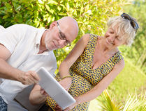 Middle age couple, smiling, using a tablet. In their garden royalty free stock images