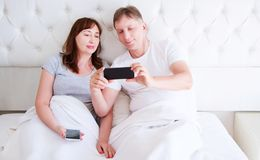 Middle age couple, woman and man using smartphone at bedroom. Ultra wide home shot stock photo
