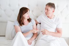 Middle age family couple talking in bed in the morning. Woman and man have dialogue. Healthy relationship. Love and romance stock image