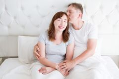 Middle age family couple in white bedroom in bed. Husband kiss wife. Love and romance. Healthy relationship.  stock images