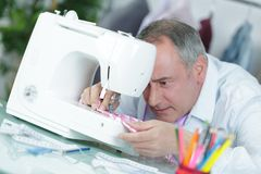 Middle-age fashion designer sewing with sewing machine Royalty Free Stock Photo