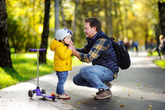 Middle age father helping his little son to put his helmet. Active toddler boy to ride a scooter. Happy family in autumn park. Middle age father helping his Royalty Free Stock Image