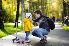 Middle age father helping his little son to put his helmet. Happy family in autumn park. Middle age father helping his little son to put his helmet. Active Royalty Free Stock Photos