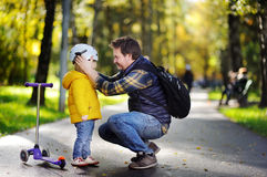 Middle age father helping his little son to put his helmet. Happy family in autumn park. Middle age father helping his little son to put his helmet. Active royalty free stock images