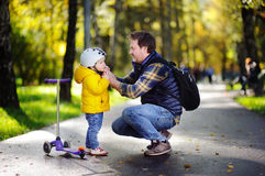 Middle age father helping his little son to put his helmet Royalty Free Stock Image