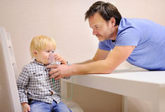 Middle age father helping his toddler son with inhalation therapy by the mask of inhaler Stock Photos