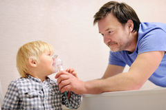 Middle age father helping his toddler son with inhalation therapy by the mask of inhaler Royalty Free Stock Image