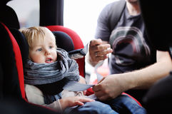 Middle age father helps his toddler son to fasten belt on car seat Royalty Free Stock Images