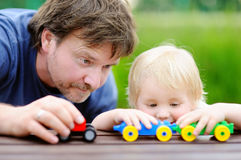 Middle age father with his toddler son playing with toy trains outdoors. Fatherhood concept stock image