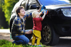 Middle age father with his toddler son washing car together outdoors stock photos