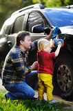 Middle age father with his toddler son washing car together outdoors Royalty Free Stock Photo