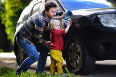 Middle age father with his toddler son washing car together outdoors Stock Image