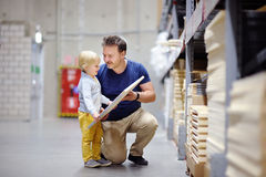 Middle age father with little boy choosing the right furniture for their apartment in a modern home furniture store Royalty Free Stock Images