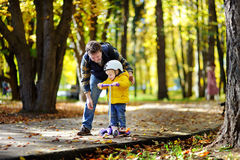 Middle age father showing his toddler son how to ride a scooter in a autumn park royalty free stock images