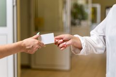 Middle age female doctor in white robe accepting White Card stock photo