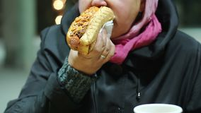 Middle age lady eating cheap street snack, addicted to high calorie junk food. Stock footage stock video footage