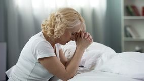 Middle-age lady praying, sitting on the floor near bed, faith and hope, religion. Stock photo royalty free stock images