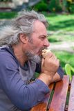 A middle age male eating an ice cream in a garden. Closeup with selective focus royalty free stock image