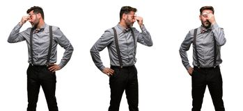 Middle age man wearing a suit. Middle age man, with beard and bow tie with sleepy expression, being overworked and tired, rubbes nose because of weariness Stock Images