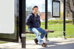Middle age man on bus stop. Middle age man sitting on bench on bus stop Stock Photos
