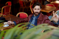 Middle age man calling waiter. Portrait of handsome hipster man with beard man asking for a bill while sitting in a restaurant terrace stock photos
