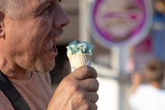 A middle age man eating ice cream on the street. stock photos
