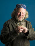 Middle age man flag bandana cash. Middle age senior long hair wearing leather motorcycle jacket American flag bandana  happy with cash money Royalty Free Stock Photos