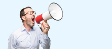 Handsome senior man  over blue background. Middle age man with glasses communicates shouting loud holding a megaphone, expressing success and positive concept Royalty Free Stock Photos