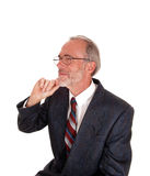 Middle age man with hand on chin. A serious portrait image of a middle age man in an suit and with glasses Stock Photography