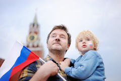 Middle age man and his little son with russian flag with Spasskaya tower Russia, Moscow on background Stock Photography