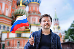 Middle age man holding russian flag. With Saint Basil`s Cathedral on background stock photography
