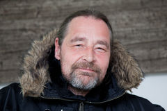 Middle Age Man in Hooded Coat Looking at Camera. Close up Smiling Middle Age Man with Goatee Beard Wearing Fur Lined Black Hooded Coat Looking at Camera Royalty Free Stock Photography
