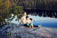 Middle age man with little cute son doing sport yoga on the top of the mountain together, happy family lifestyle people Stock Photos