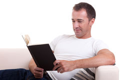 Middle-age man lying on the sofa reading a book Royalty Free Stock Photos