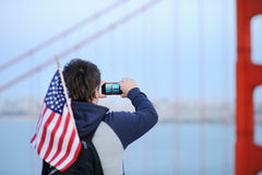 Middle age man making mobile photo on Golden Gate bridge. Middle age man with american flag in backpack making mobile photo on famous Golden Gate bridge in San Royalty Free Stock Photos