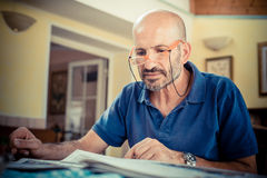 Middle age man reading newspaper Stock Photography