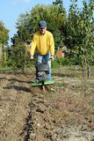 Middle age man with a rototiller. In the garden Stock Photography
