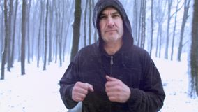 Middle age man running outdoor on a snowy day. Motivational, healthy way of life.
