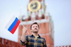 Middle age man with russian flag with Spasskaya tower Russia, Moscow on background Royalty Free Stock Photo