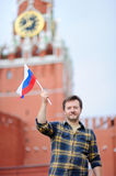 Middle age man with russian flag with Spasskaya tower Russia, Moscow on background Royalty Free Stock Image