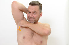 Middle-age man shaving his underarm Stock Images
