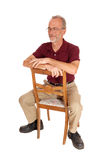 Middle age man sitting backwards on chair. Royalty Free Stock Images