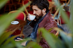 Middle age man sitting in a restaurant waiting for his wife. Side view through plant leaves, pensive fashionable hipster man holding cup of tea or coffee next to royalty free stock photos