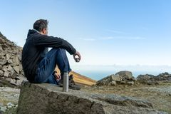 Middle age man sitting on the rock drinking a tea or coffee in cold morning looking on the vale and sea from mountain range, view stock image