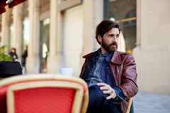 Middle age man sitting on the terrace of the hotel expensive. Portrait of handsome and stylish man with beard enjoying a cup of coffee in a coffee shop, adult stock images