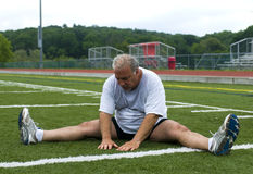 Middle age man stretching on sports field Royalty Free Stock Photography