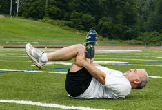 Middle age man stretching on sports field Stock Images