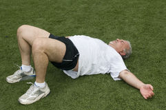 Middle age man stretching sports field. Overweight middle age retired and active senior man stretching his back muscles after exercising on a sports field royalty free stock photos